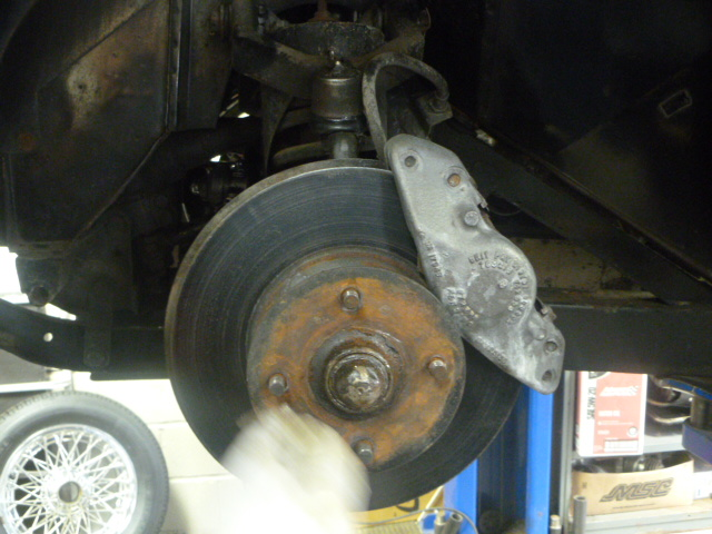 In the process of re-mounting the wheels.  Dean's blurry hand is scraping away some rust.  The wheel bearings on the car were a bit too tight, so Dean set them back like they're supposed to be.